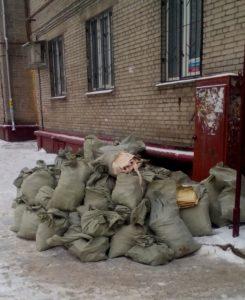 Строительный мусор в зеленых мешках возле подъезда